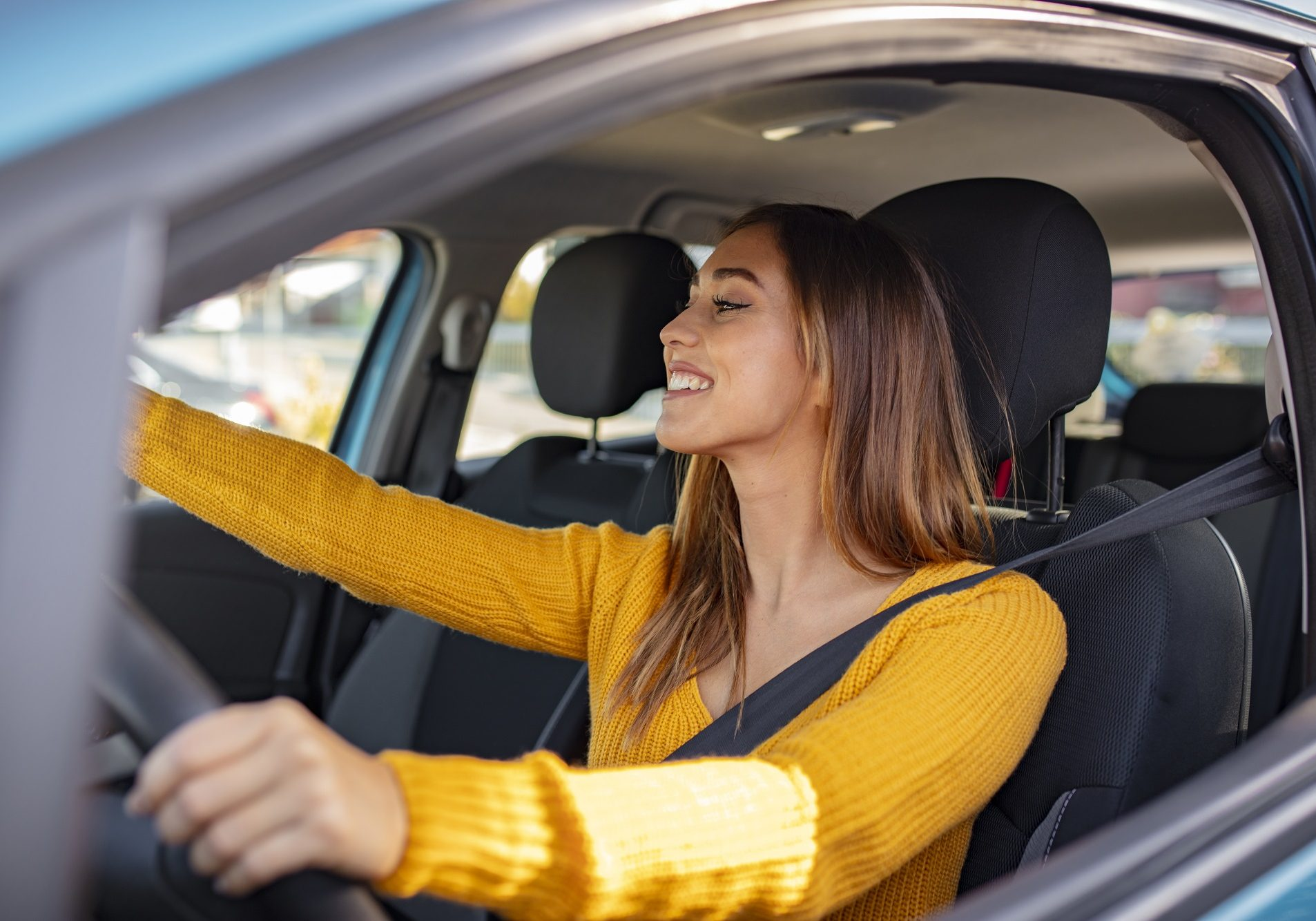 Beautiful female Driver adjusting the Rear Mirror looking at herself. Adjusting the rear view mirror. Woman adjusts the rear view mirror with her hand. Happy young woman driver looking adjusting rear view car mirror